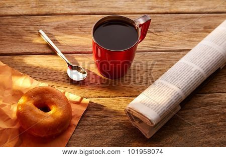Coffee red cup newspaper and dona morning breakfast on vintage wooden table