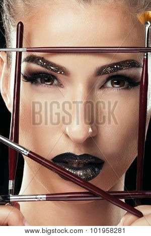 Woman With Make Up Brushes And Black Lips