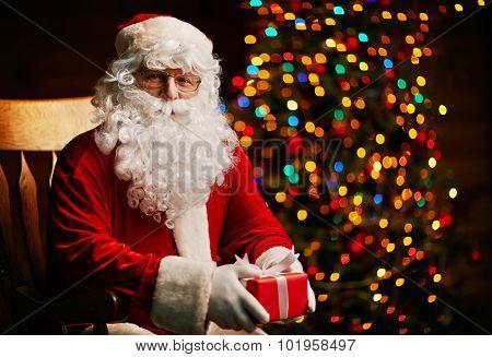 Santa Claus with small giftbox looking at camera