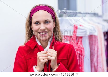 Portrait of smiling woman wearing red coat in clothing store
