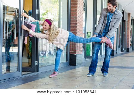 Smiling man trying to pull away his girlfriend from clothes store at shopping mall