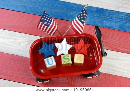 A childs toy wagon with red white and blue stars and blocks spelling USA. American Flags are behind the wagon on a patriotic red white and blue wood picnic table. Great for American holiday projects.