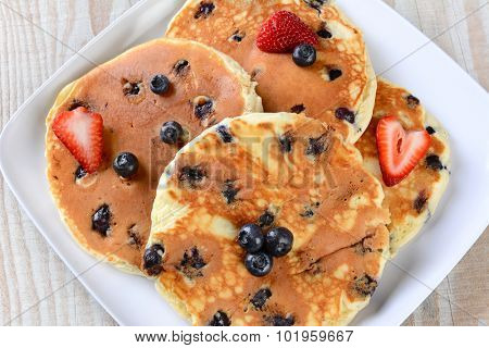 Overhead closeup view of a plate full of fresh homemade pancakes with blueberries and strawberries.
