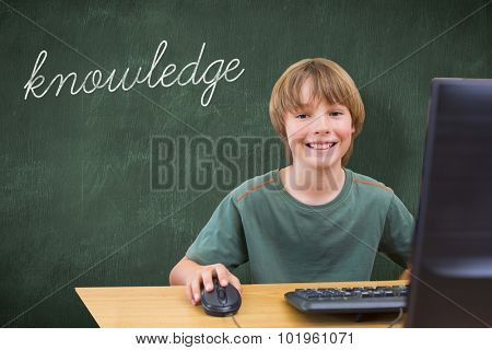 The word knowledge and school kid on computer against green chalkboard