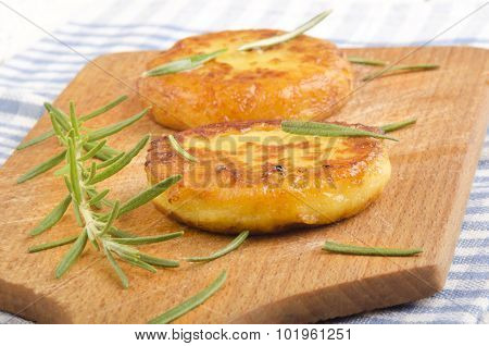 Potato Pancake With Rosemary On Wooden Board