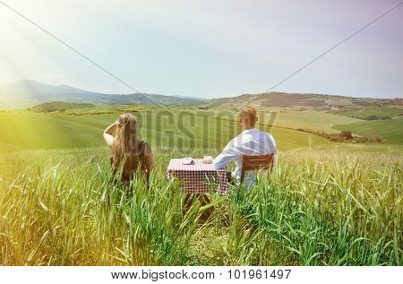 A couple at the table in the middle of a Tuscan field. Italy