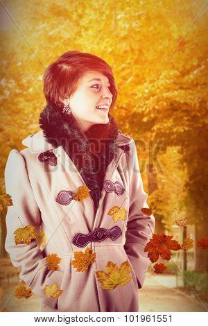 Smiling beautiful woman in winter coat against autumn scene