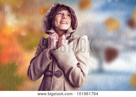Smiling beautiful woman in winter coat looking up against autumn turning to winter