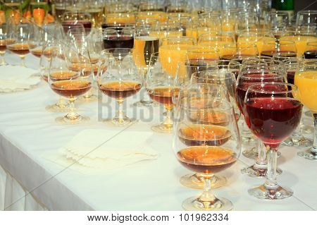 lot of wine glasses with alcoholic drinks on the table