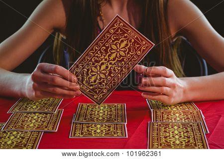 Fortune teller using tarot cards on black background