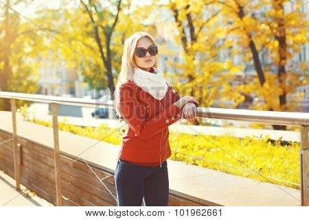 Fashion Young Woman Wearing A Sunglasses And Red Leather Jacket With Scarf In Sunny Autumn City