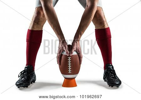 Low section of sports player placing the ball between his legs against white background