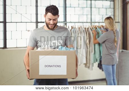 Man holding clothes donation box with woman seen in background at office