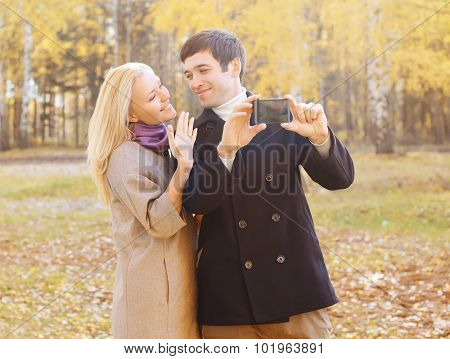 Portrait Of Happy Smiling Young Couple Making Selfie On Smarphone In Autumn Park