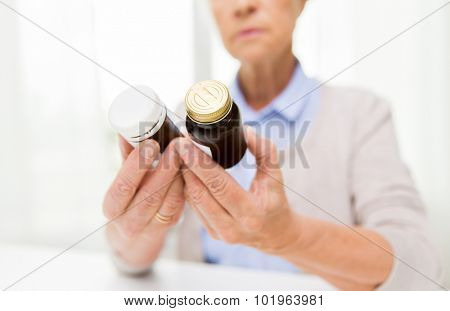 age, medicine, health care and people concept - close up of senior woman looking at jars with medicine at home or hospital office