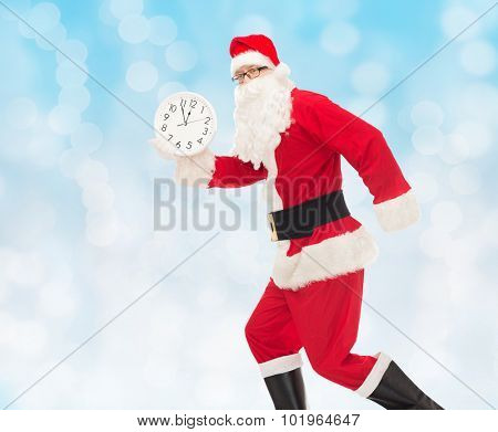 christmas, holidays and people concept - man in costume of santa claus running with clock showing twelve over blue lights background
