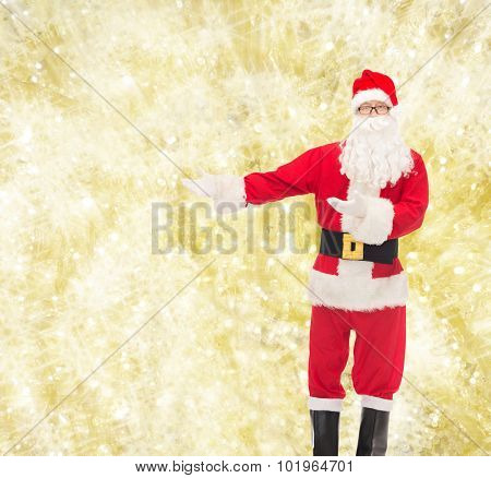 christmas, holidays, gesture and people concept - man in costume of santa claus over yellow lights background