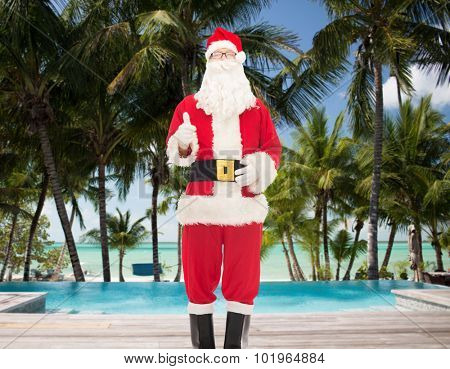 christmas, holidays, gesture, travel and people concept- man in costume of santa claus showing thumbs up over swimming pool on tropical beach background