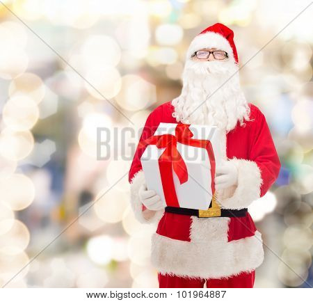 christmas, holidays and people concept - man in costume of santa claus with gift box over lights background