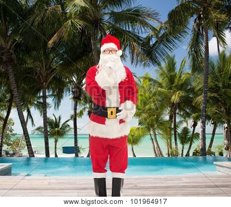 christmas, holidays, travel and people concept - man in costume of santa claus making hush gesture over swimming pool on tropical beach background