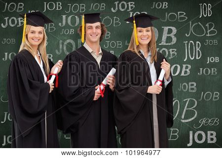 Three smiling students in graduate robe holding a diploma against green chalkboard