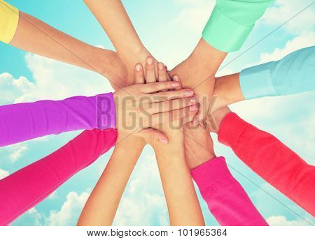 people, gesture, gay pride and homosexual concept - close up of women hands in rainbow clothes on top of each other over blue sky background