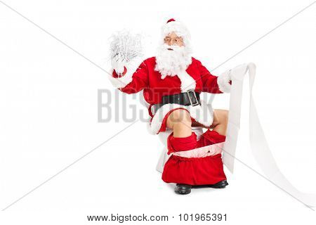Santa Claus holding a pile of shredded paper in one hand and a long blank list in the other seated on a toilet isolated on white background