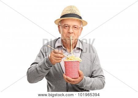 Joyful senior eating Chinese noodles from a paper box and looking at the camera isolated on white background