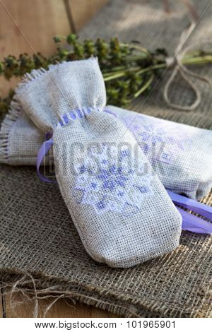 Sachet with ukrainian embroidery, sheaf of wheat and dried herbs on wooden background, close-up