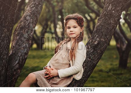 adorable thoughtful kid girl in beige outfit climbing apple tree in spring garden