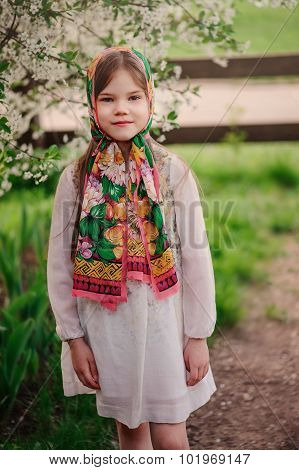 spring portrait of adorable dreamy child girl in tradition shawl at blooming apple tree
