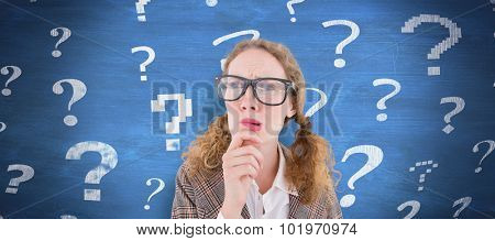 Geeky hipster woman thinking with hand on chin against blue chalkboard