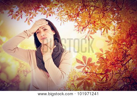 Sick brunette touching her throat and her head against autumn scene