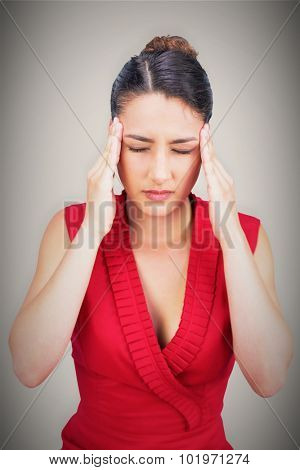 Sexy tied haired brunette having headache against grey background with vignette