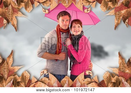Couple standing underneath an umbrella against mountain peak through the clouds
