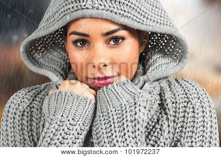 Pretty girl in winter jumper looking at camera against country scene