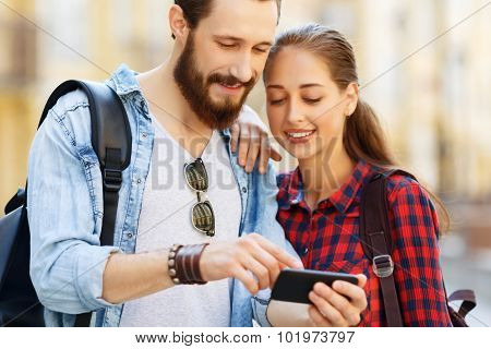 Pleasant couple holding mobile phone