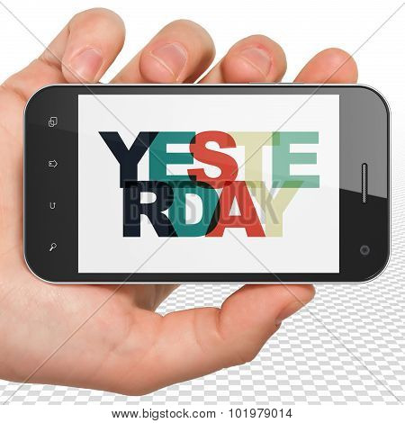 Time concept: Hand Holding Smartphone with Yesterday on  display