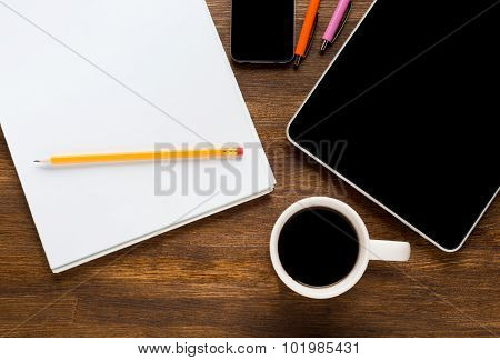 Tablet computer with stickers,cup of coffee and on the wooden table
