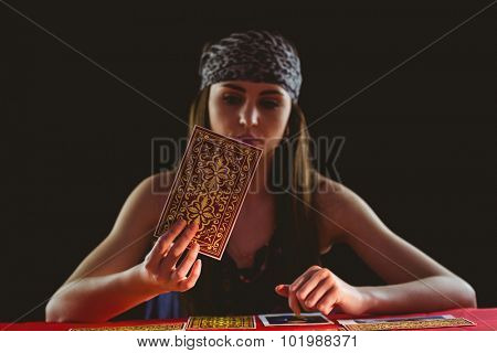 Fortune teller using tarot cards on black background