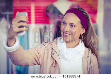 Smiling woman taking selfies at shopping mall