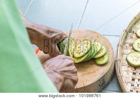 Old man hand cutting Bale fruit on wooden chopping block