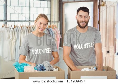 Portrait of smiling volunteers separating donations clothes in office