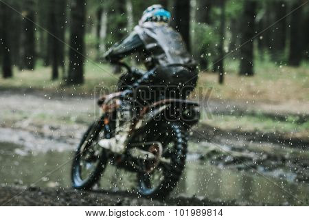 Motocross bike crossing creek, water splashing