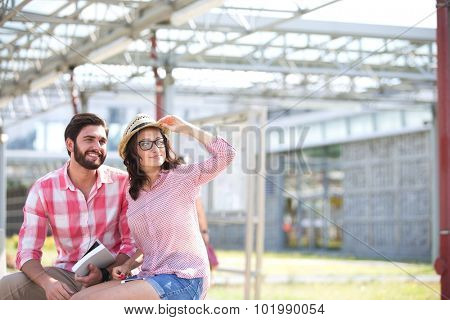 Happy couple looking away while sitting on bench under shade