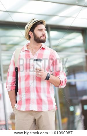 Thoughtful man looking away while holding disposable cup in city
