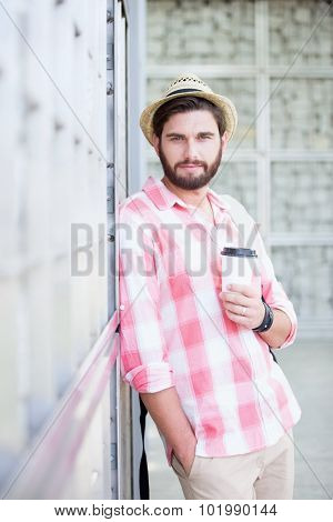 Portrait of confident man holding disposable cup while leaning on wall