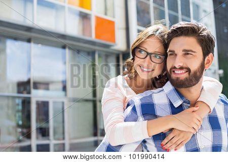 Loving man piggybacking woman in city