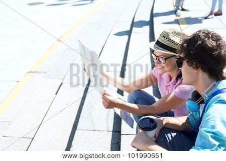 Happy couple reading map while sitting on steps outdoors