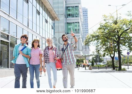 Happy man showing something to friends while walking in city